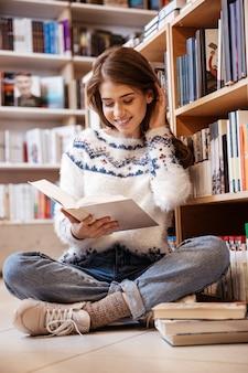 Молодая студентка сидит на полу библиотеки и читает книгу в колледже