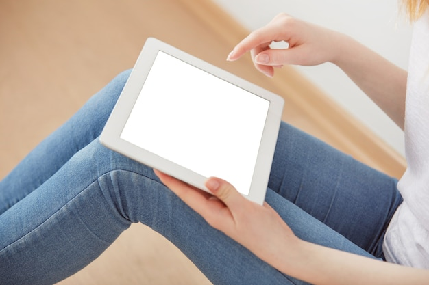 Young female student sitting in a university recreation hall using touch pad