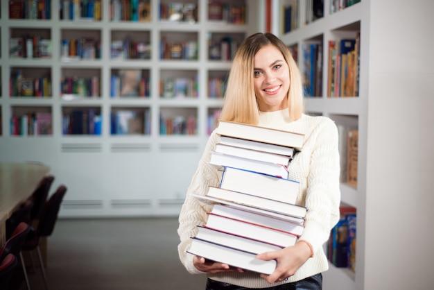 Молодая студентка учится в школьной библиотеке с множеством книг в руках.