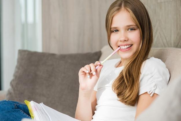 若い女子学生がコンピューター、ノートブック、鉛筆を使って勉強し、家のインテリアで練習問題を書く