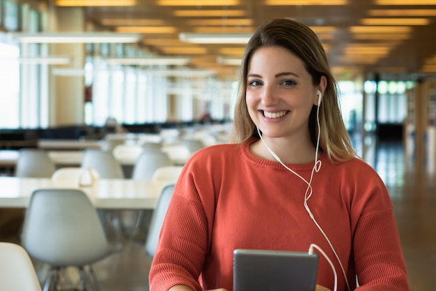 Молодая студентка учится в библиотеке.