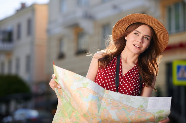 Young female student or traveler with camera and paper city map walking outdoors and looking for something