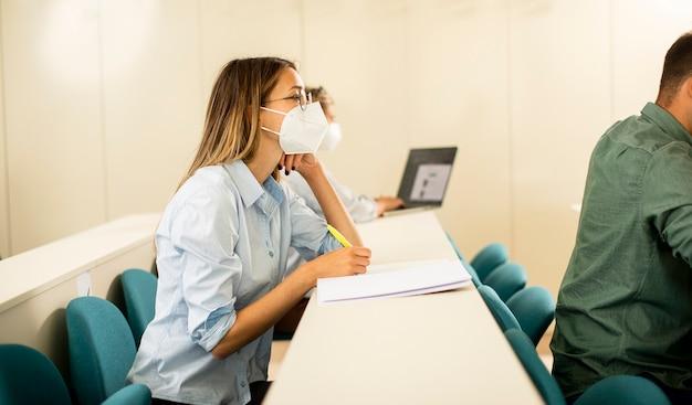 講堂でウイルス対策のための顔面保護医療マスクを着用した若い女子学生