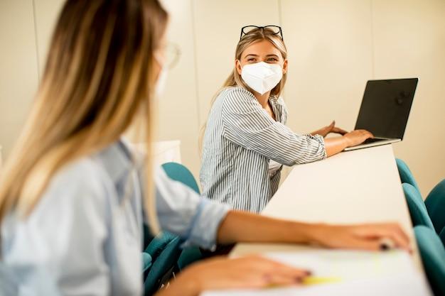 講堂でウイルス対策のための顔面保護医療マスクを身に着けている若い女子学生