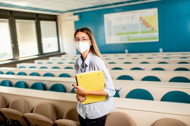 講堂に立っているウイルス対策のための顔面保護医療マスクを身に着けている若い女子学生