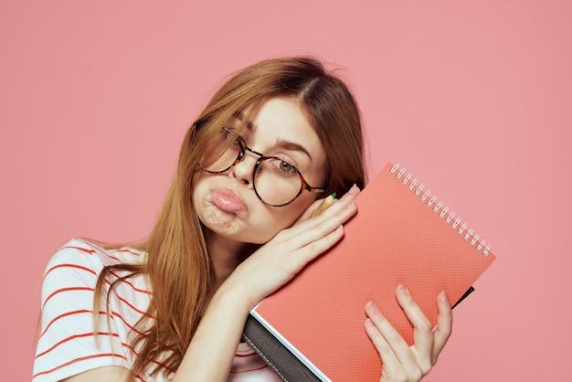 Молодая студентка с книгами на розовом фоне