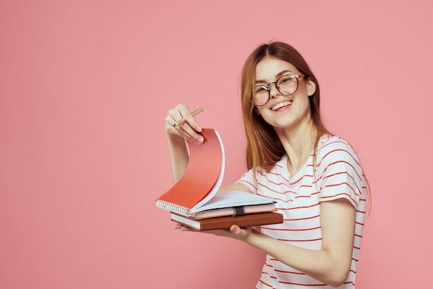 Молодая студентка с книгами в розовых очках на лице института образования обрезанное.