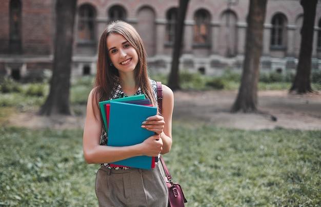 Молодая студентка с разноцветными тетрадями возле кампуса и улыбается