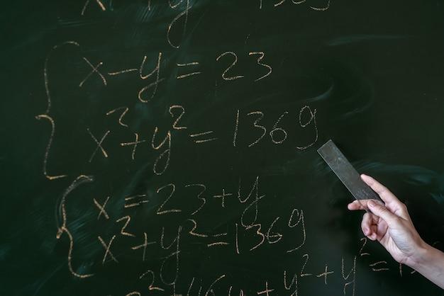 칠판에 수학 공식을 쓴 젊은 여학생, 교육 개념