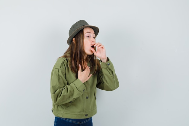 Young female suffering from cough in jacket, pants, hat and looking sick. front view.