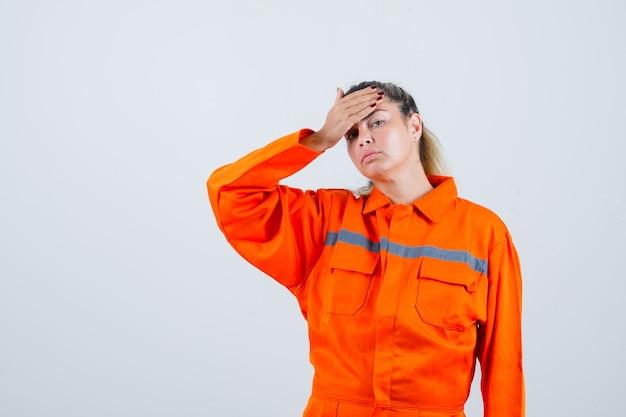 작업자 유니폼을 입고 두통으로 고통 받고 불편한 젊은 여성. 전면보기.