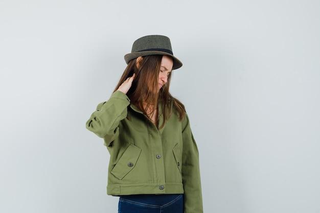 Giovane donna che soffre di dolore al collo in giacca, pantaloni, cappello e sembra stanca. vista frontale.
