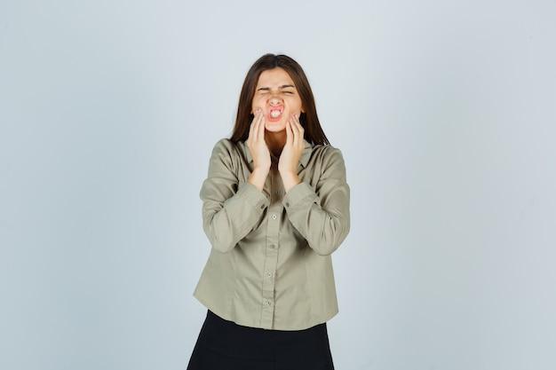 Giovane donna che soffre di doloroso mal di denti in camicia, gonna e che sembra a disagio