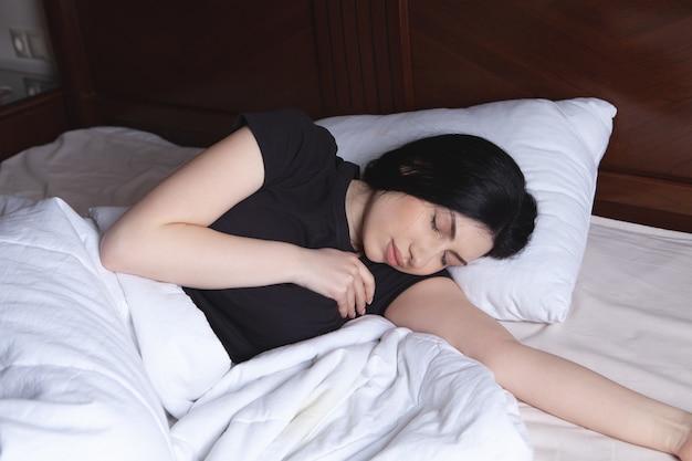 Молодая женщина страдает от сильной боли в груди