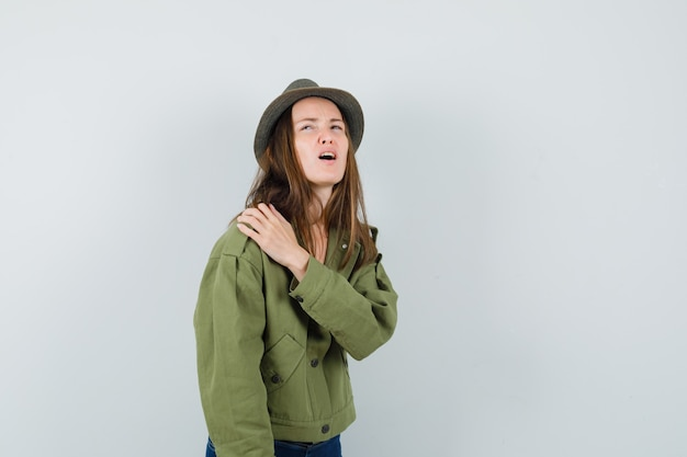 Young female suffering from shoulder pain in jacket, pants, hat and looking fatigued. front view.