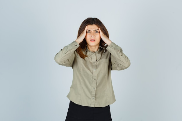 Молодая женщина в рубашке страдает от сильной головной боли и выглядит раздраженной