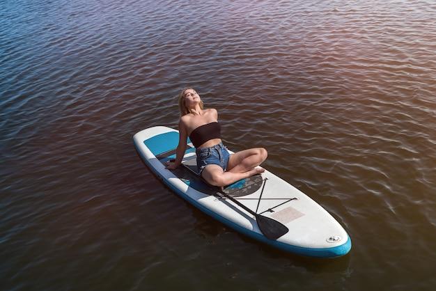 スタンドアップパドルボードに横たわって自然に休む若い女性サーファー、夏の自由