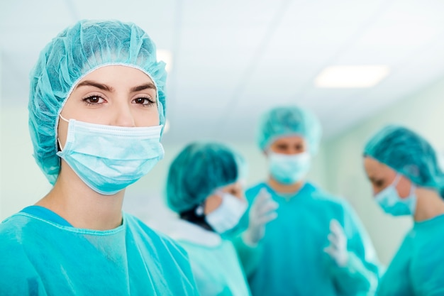 Young female surgeon with medical team in back before surgery