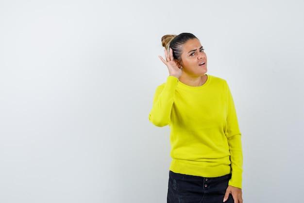 Giovane donna in maglione, gonna di jeans che tiene la mano dietro l'orecchio e sembra meravigliata