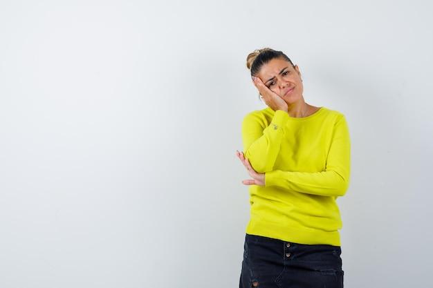 Giovane donna in maglione, gonna di jeans che si appoggia sulla guancia e sembra pensierosa