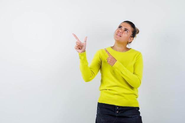 Giovane donna in maglione, gonna di jeans che punta da parte e sembra concentrata