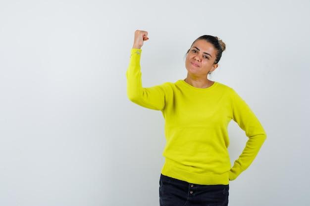 Giovane donna in maglione, gonna di jeans che alza il pugno e sembra sicura