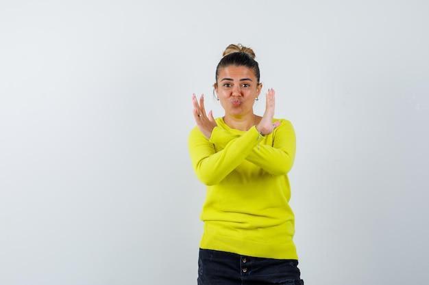 Giovane donna in maglione, gonna di jeans che mostra il gesto di arresto e sembra sicura