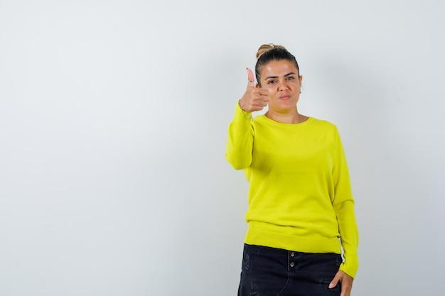 Giovane donna in maglione, gonna di jeans che mostra pollice in su e sembra sicura