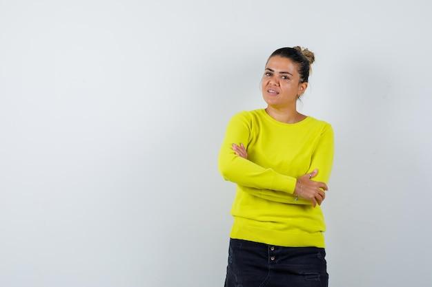 Giovane donna in maglione, gonna di jeans in piedi con le braccia incrociate e dall'aspetto fiducioso