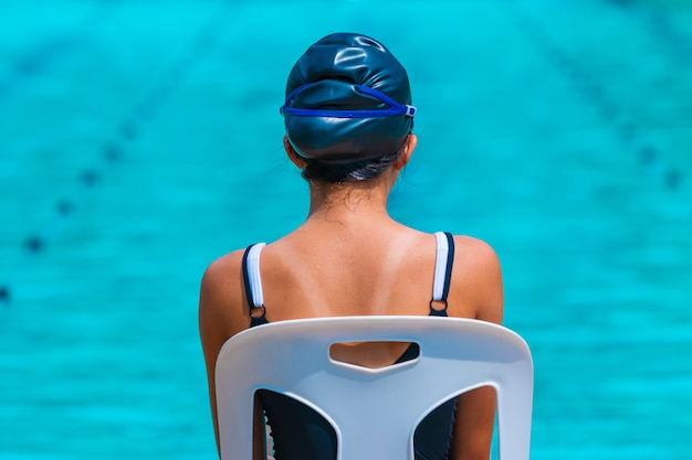 Young female swimmer sitting on a white beach chair looking at the swimming pool