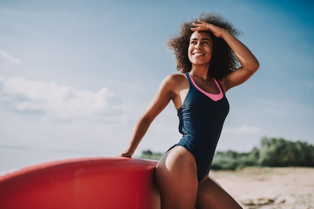 Young female in swimsuit lean on surf at beach.