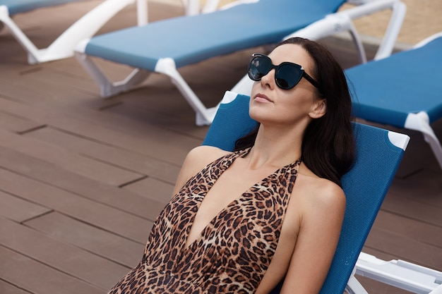 Young female in swimsuit with leopard print relaxing on blue lounge chair, wearing black sunglasses, looks relaxed