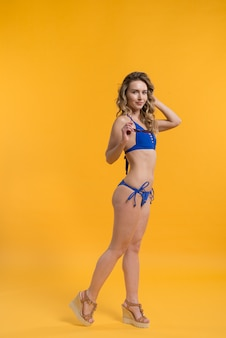 Young female in swimwear posing with sunglasses