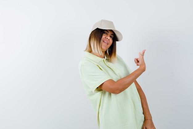 Giovane donna in t-shirt, cappuccio rivolto indietro e guardando fiducioso, vista frontale.