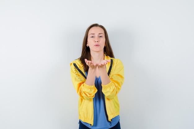 Giovane donna in t-shirt, giacca che soffia aria bacio con labbra imbronciate e dall'aspetto carino, vista frontale.