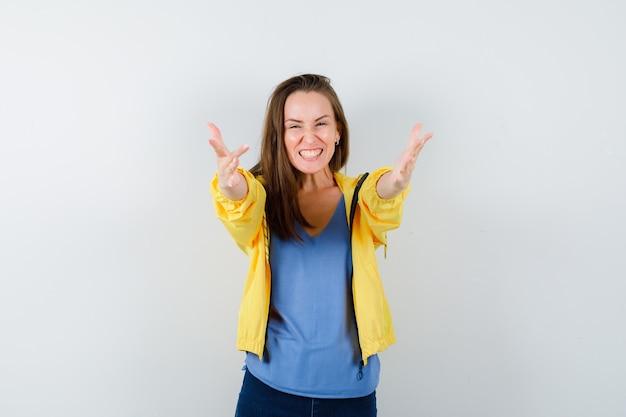 Giovane donna in t-shirt, giacca che apre le braccia per un abbraccio e sembra felice, vista frontale.