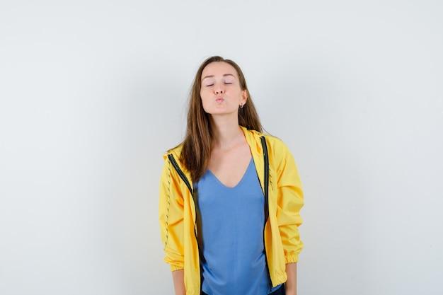 Giovane donna in t-shirt, giacca che fa il broncio, chiude gli occhi e sembra attraente, vista frontale.