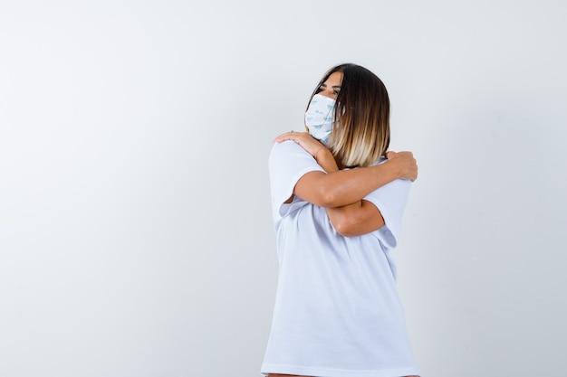 Giovane donna in t-shirt, maschera che si abbraccia e che sembra carina, vista frontale.