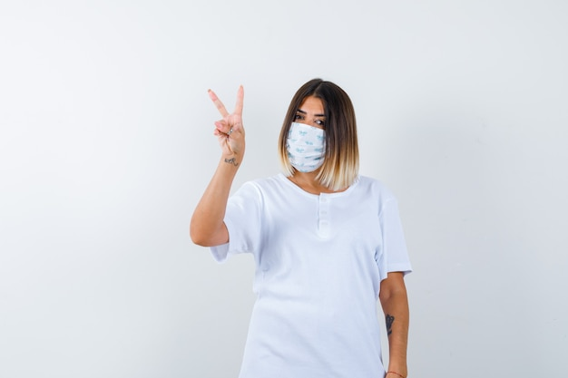 Young female in t-shirt, mask showing victory sign and looking lucky , front view.