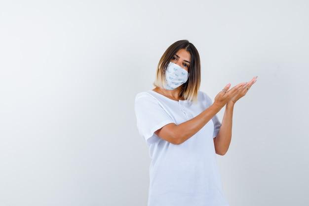 Giovane donna in t-shirt, maschera che dà il benvenuto a qualcosa e sembra fiduciosa, vista frontale.