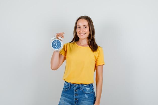 Giovane donna in t-shirt, pantaloncini tenendo sveglia e sorridente