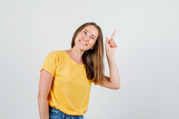 Giovane donna in t-shirt, pantaloncini guardando da parte con il dito in alto e guardando allegro