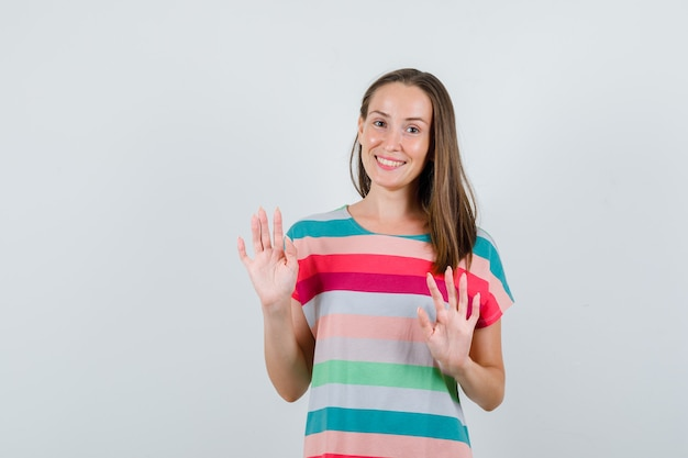 Young female in t-shirt showing refusal gesture politely , front view.