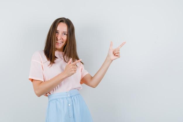 Giovane donna in t-shirt, gonna che mostra il gesto della pistola e sembra allegro, vista frontale.
