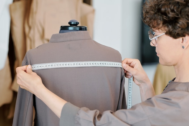 Молодая женщина-портной измеряет ширину спины серого пиджака на манекене во время работы в студии