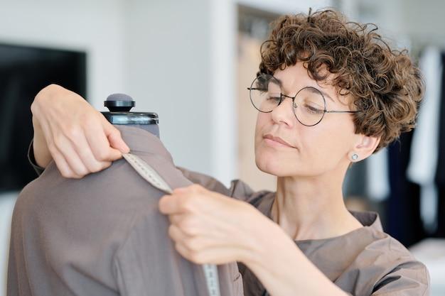 ワークショップでマネキンに未完成のジャケットの肩の長さを測定する若い女性のテーラー