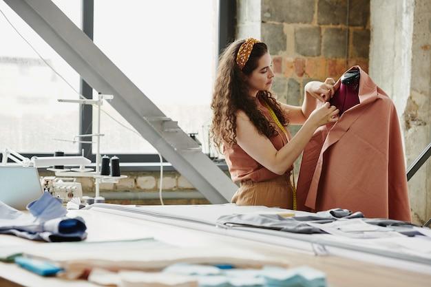 茶色の布で包まれたダミーのそばに立って、新しい注文に取り組んでいる間、その端を固定している若い女性の仕立て屋