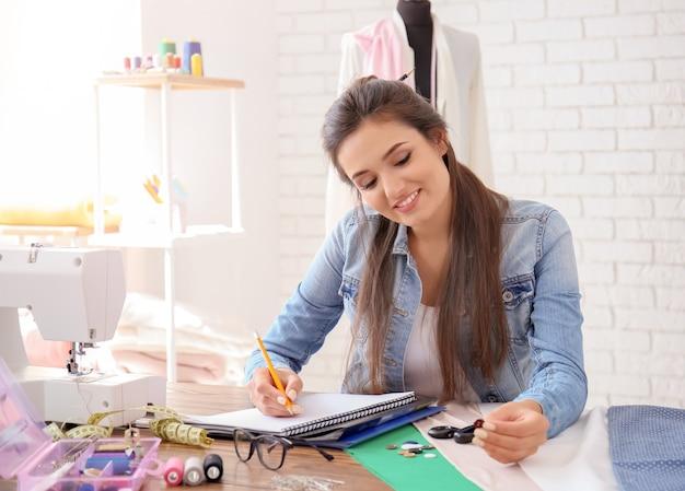 アトリエのテーブルで働く若い女性のテーラー