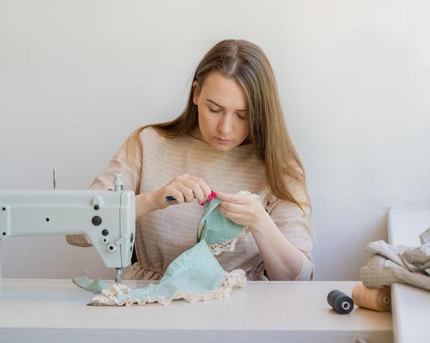 Молодая женщина-портной работает над новой одеждой на своем рабочем месте в студии
