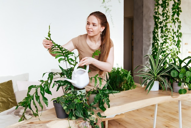 Молодая самка ухаживает и поливает комнатные растения. уход за растениями в домашних условиях